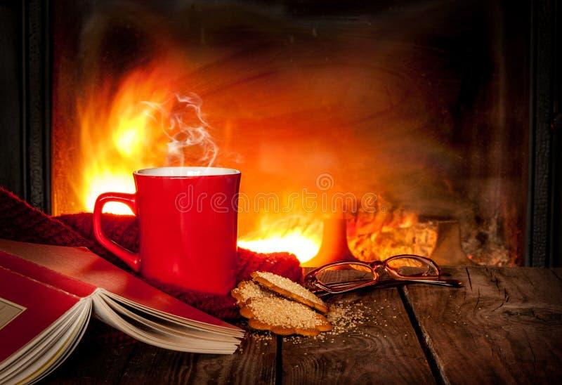 Hete thee of koffie in een rode mok, een boek en een open haard