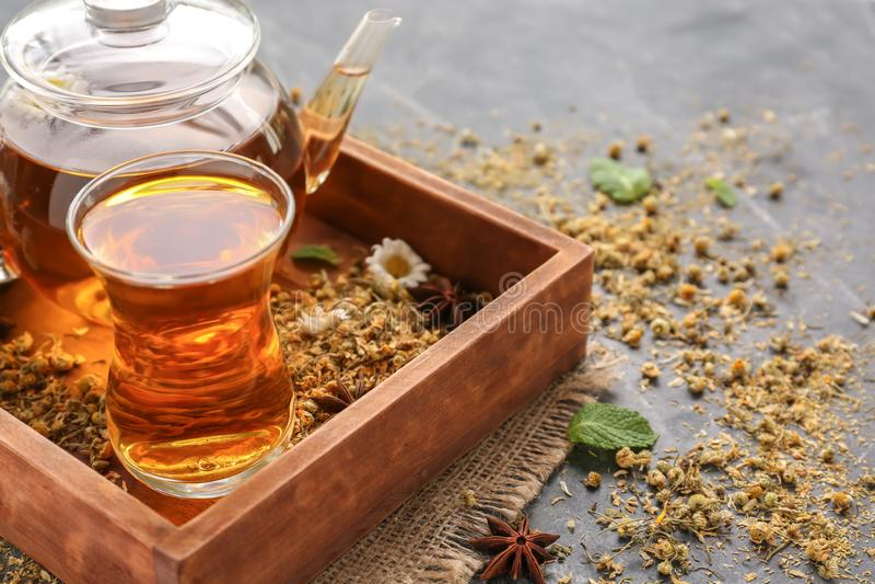 Hete thee met droge kamillebloemen in houten doos royalty-vrije stock foto