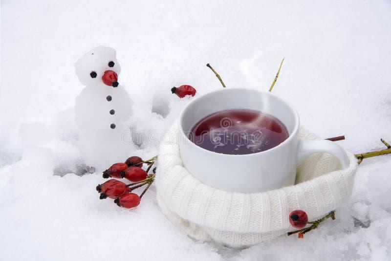 Hete thee met rode rozebottels in sneeuw en een kleine sneeuwman, vi royalty-vrije stock fotografie