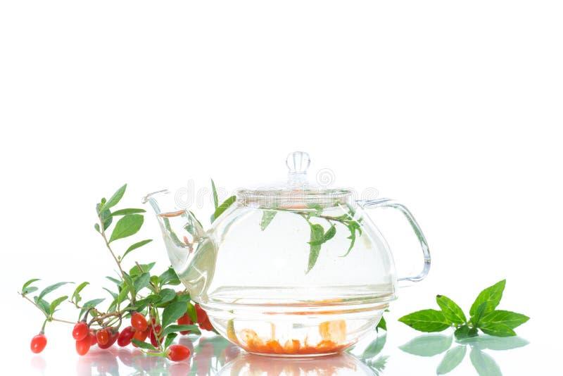 Hete thee van rijpe rode gojibessen in een glastheepot royalty-vrije stock afbeelding