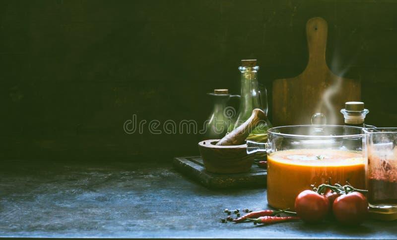 Hete tomatensoep met stoom in glaspot op rustieke lijst bij donkere muurachtergrond met het koken van ingrediënten Keukenscène, n stock afbeeldingen