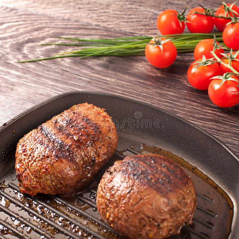 Hete verse lapjes vlees op pan stock afbeeldingen