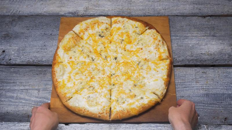 Hete vier kazen heerlijke pizza die op een dienblad op houten grijze raadsachtergrond liggen Kader Sluit omhoog voor handen zette royalty-vrije stock fotografie
