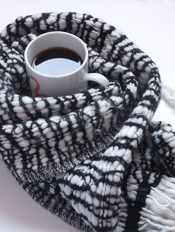 Hete zwarte koffie met gevormde zwart-witte sjaal op wit bureau Vlak leg Hoogste mening stock afbeeldingen