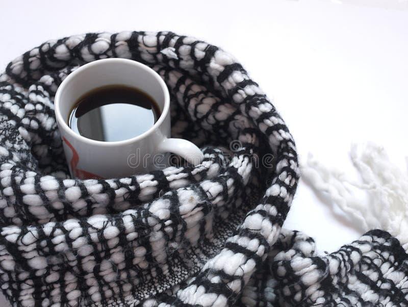 Hete zwarte koffie met gevormde zwart-witte sjaal op wit bureau Vlak leg Hoogste mening royalty-vrije stock foto