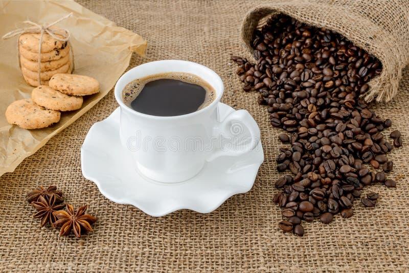 Hete zwarte koffie in witte elegante kop met zich schotel, zoete koekjes en het verspreiden van koffiebonen op landelijke juteach royalty-vrije stock foto
