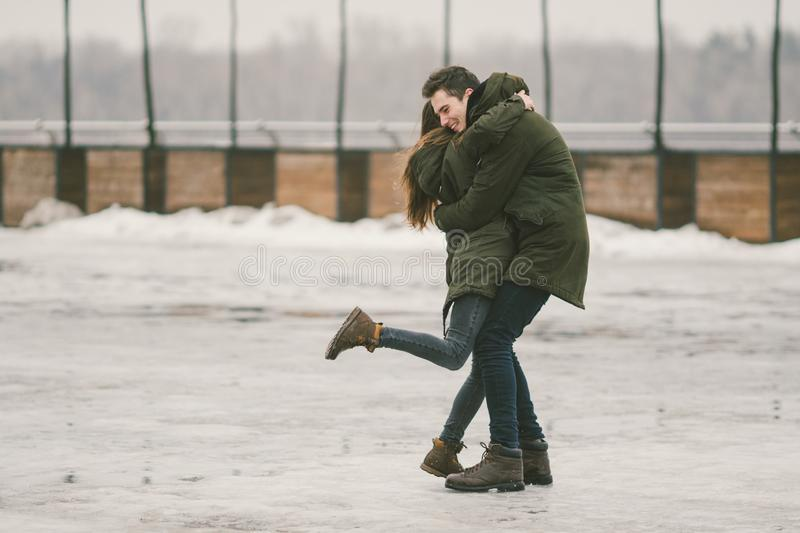 A heterosexual couple young people in love students a man and a Caucasian woman. In winter, in the city square covered with ice, royalty free stock photography