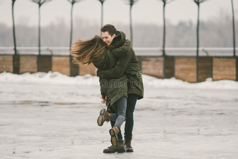 A heterosexual couple young people in love students a man and a Caucasian woman. In winter, in the city square covered with ice, royalty free stock images