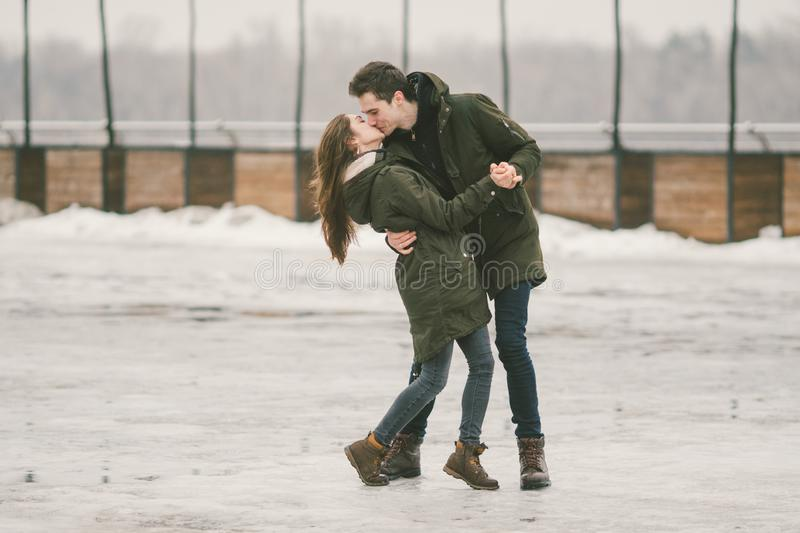 A heterosexual couple young people in love students a man and a Caucasian woman. In winter, in the city square covered with ice, stock image