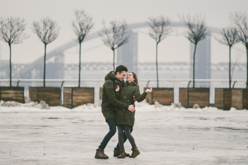 A heterosexual couple young people in love students a man and a Caucasian woman. In winter, in the city square covered with ice, royalty free stock photos