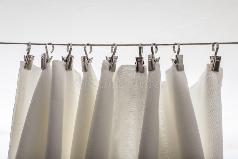 Hetgekleurde gordijn hangen op een koord op metaalhaken stock foto