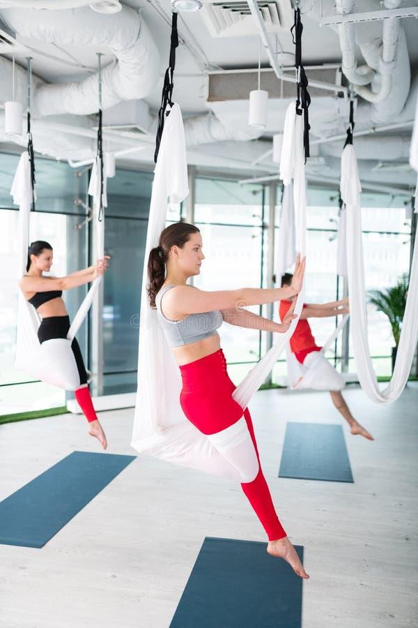 Hethaired yogatrainer aardig tonen stelt voor luchtyoga stock foto
