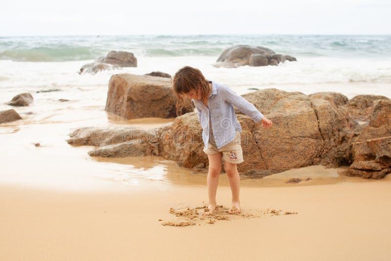 Hetoude meisje spelen op het zandige strand van het overzees royalty-vrije stock fotografie