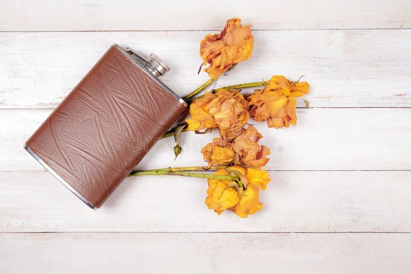 Heupfles met geverfte rozen stock afbeelding