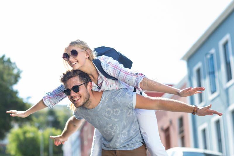 Heupmens die op de rug aan zijn meisje geven royalty-vrije stock afbeelding