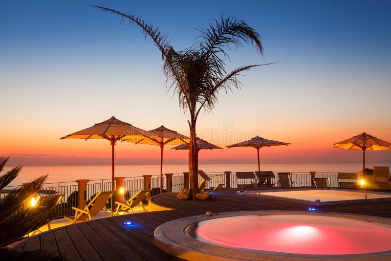 Heure d'été : belle vue d'aube rouge à l'espace piscine avec la paume photos libres de droits