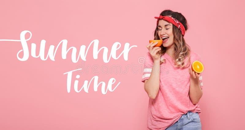 Heure d'été d'inscription La belle jeune fille dans le T-shirt rose, conserve l'orange drôle sur le fond rose photo libre de droits