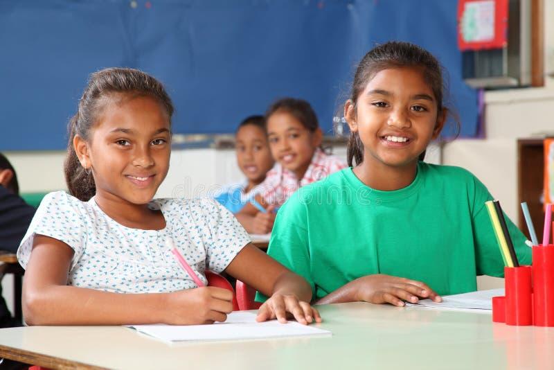 Heure d'apprendre deux filles gaies d'école dans la classe photos stock