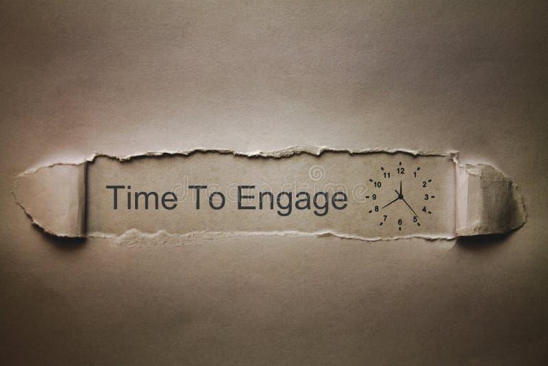 Heure d'engager le mot avec l'horloge sur le papier déchiré images stock