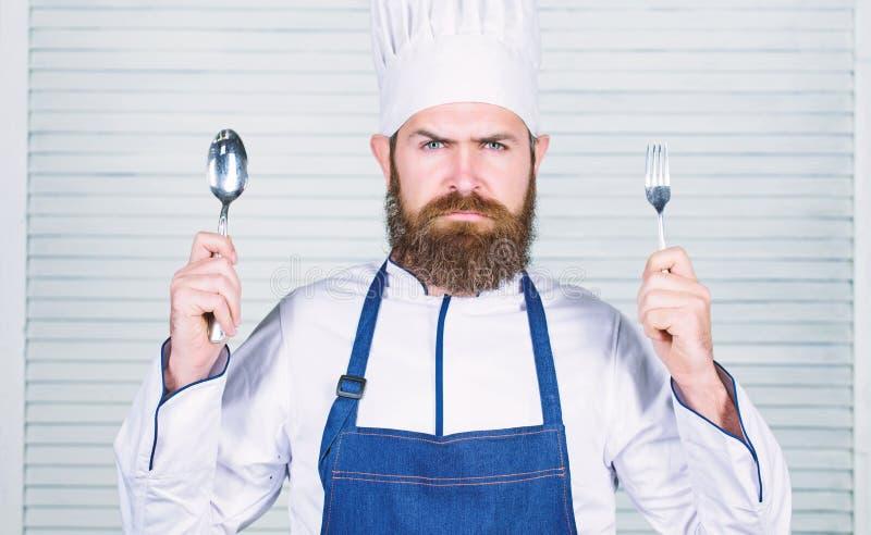 Heure d'essayer le go?t Cuill?re et fourchette s?rieuses de prise de visage de chef L'homme beau avec la barbe tient la vaisselle photo stock