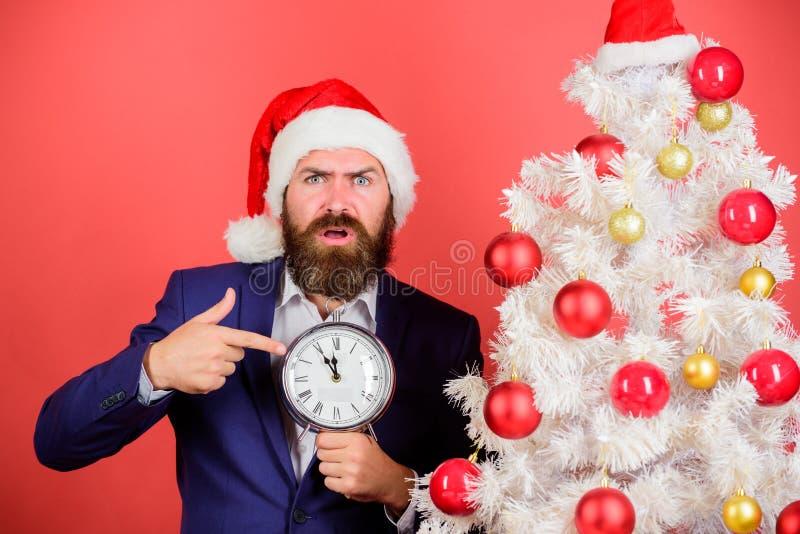 Heure de célébrer Costume d'usage d'homme et horloge barbus de prise de chapeau de Santa L'homme d'affaires joignent la célébrati image libre de droits