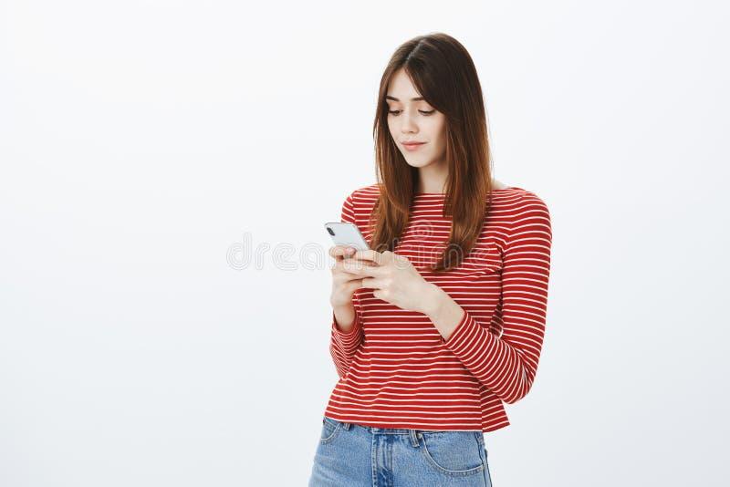 Heure de faire la première étape et de l'appeler Femme belle focalisée dans l'équipement occasionnel, tenant le smartphone et int image libre de droits