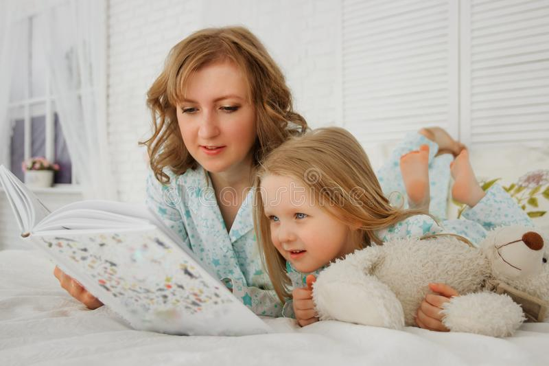 Heure du coucher de lecture de famille Mère assez jeune lisant un livre à sa fille La mère lit un conte de fées à sa fille a photos libres de droits
