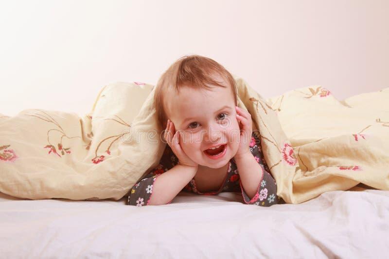 Heure du coucher (jeune fille se trouvant sur le lit sous les couvertures) image stock