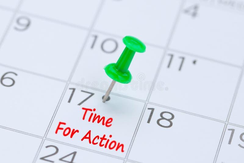 Heure pour l'action écrite sur un calendrier avec une goupille verte de poussée à r photo stock