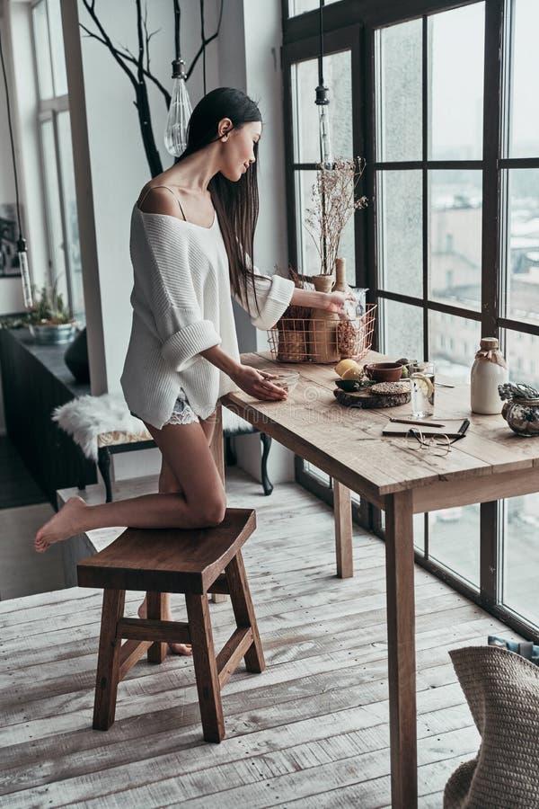 Heure pour le petit déjeuner intégral de la jeune femme attirante prepar images stock