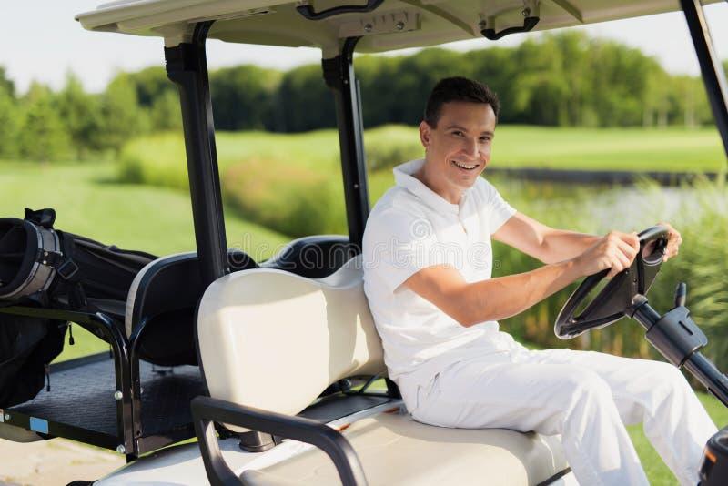 Heure pour un jeu du golf Un homme dans un costume blanc monte un chariot de golf blanc image libre de droits
