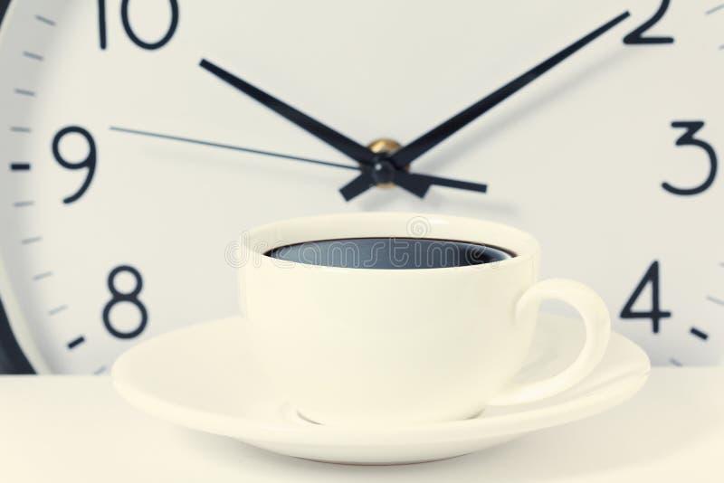 Heure pour une pause-café, le travail avec la tasse de café et l'horloge à l'horloge de dix o sur le blanc images stock
