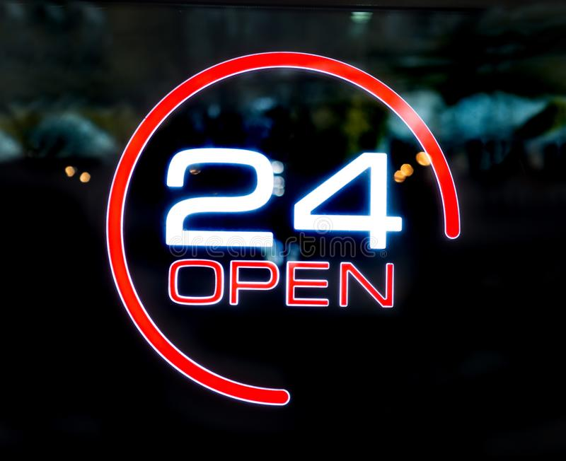 24 heures ouvertement écrites sur la porte en verre image stock