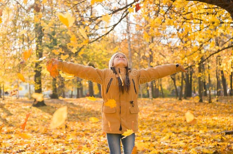 Heureuse adorable petite fille jetant les feuilles mortes, jouant dans le parc d'automne image libre de droits