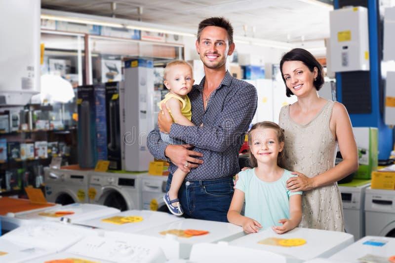 Heureuse famille avec les marchandises de achat d'enfants dans le ménage photographie stock libre de droits