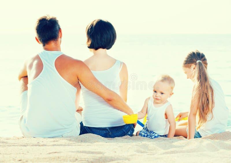 Heureuse famille et enfants s'asseyant avec en avant arrière photo libre de droits