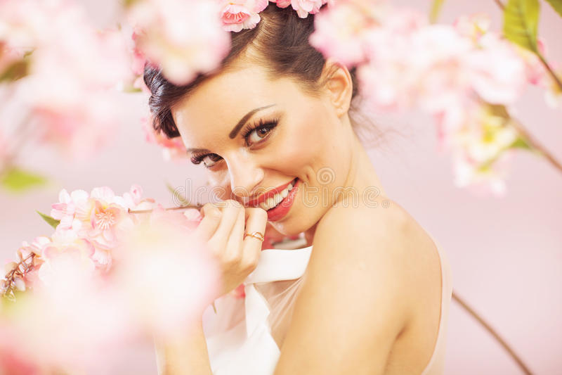 Heureuse femme de sourire avec des fleurs dans les cheveux image stock