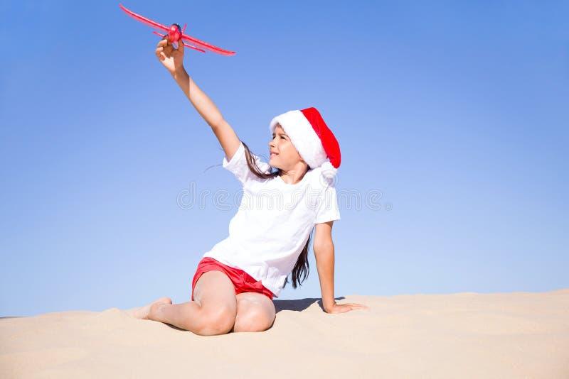 Heureuse petite fille mignonne portant un chapeau de Santa rouge assise sur la plage de sable au bord de la mer et jouant avec l' images libres de droits