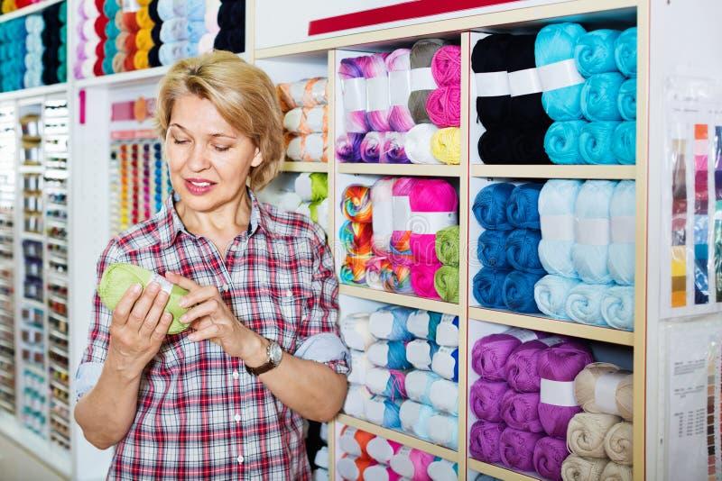 Heureux client mûr de femme sélectionnant le divers fil photographie stock