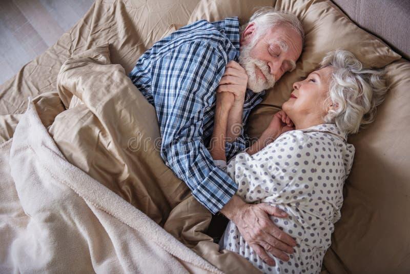 Heureux couples pluss âgé dormant et étreignant à l'intérieur image libre de droits