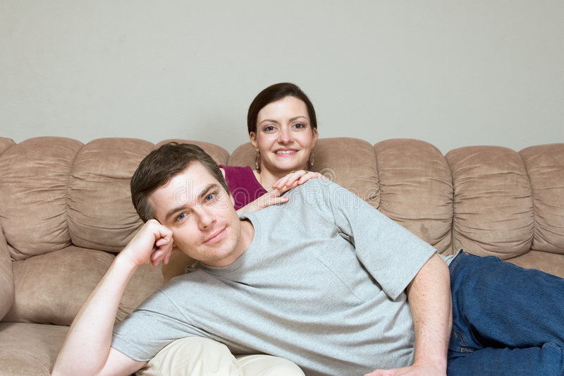 Heureux, couples se reposant sur un divan - horizontal photographie stock libre de droits