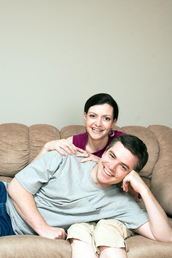 Heureux, couples se reposant sur un divan - verticale photographie stock libre de droits