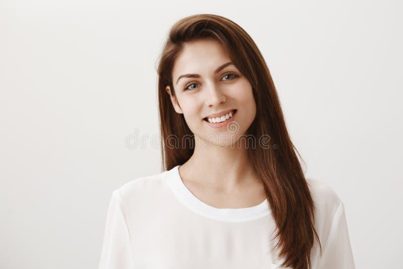 Heureux d'être par votre côté Le studio a tiré de la soeur caucasienne belle optimiste souriant et inclinant la tête comme auditi photographie stock libre de droits