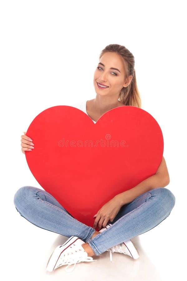 Heureux dans la jeune fille d'amour tenant le grand coeur rouge image libre de droits