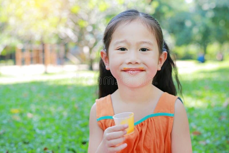 Heureux de la petite fille buvant du jus d'orange avec souillé autour de sa bouche dans le jardin d'été photos libres de droits