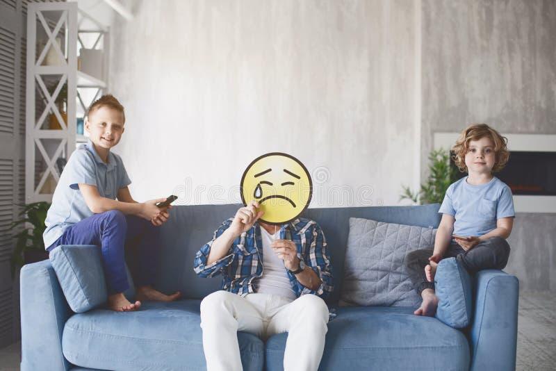 Heureux enfants et père malheureux à la maison photo libre de droits