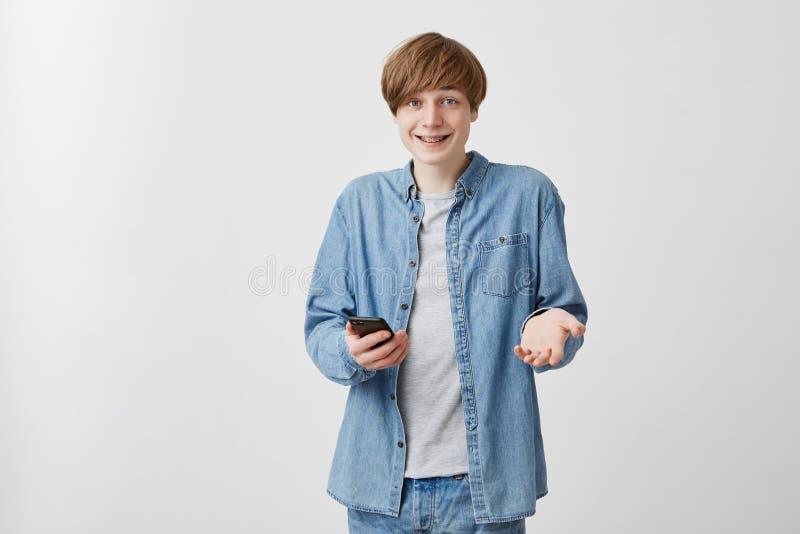 Heureux mâle avec les cheveux justes se tenant à l'intérieur avec son smartphone causant avec des amis Jeune homme positif dans o images stock