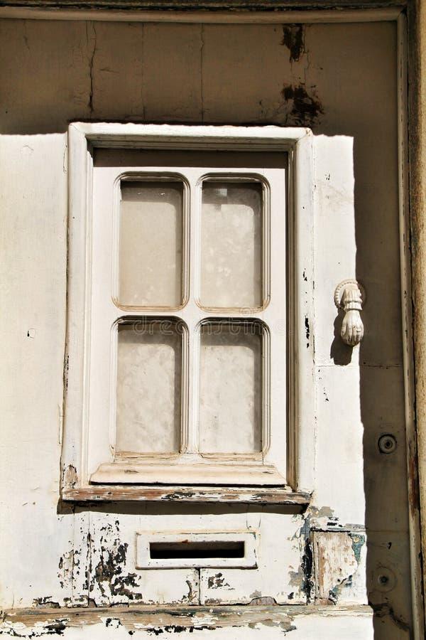 Heurtoir avec la forme de main sur la vieille porte en bois photographie stock