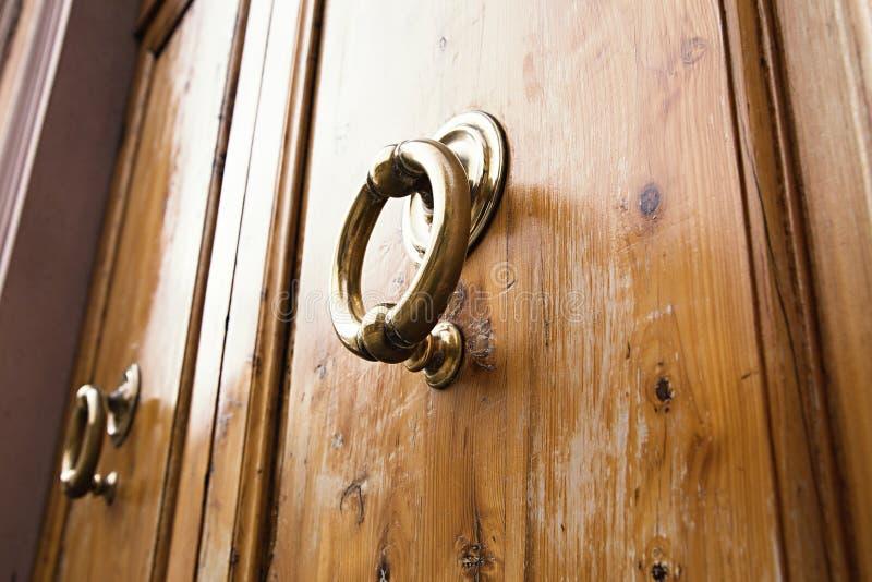 Heurtoir d'anneau en laiton sur la vieille porte en bois image libre de droits