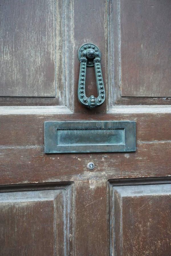 Heurtoir de porte en bronze antique sur une porte brune superficielle par les agents photographie stock